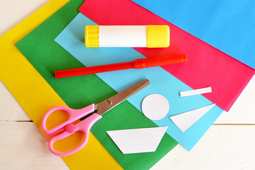 A pritt stick, scissors and a pen laid on coloured card