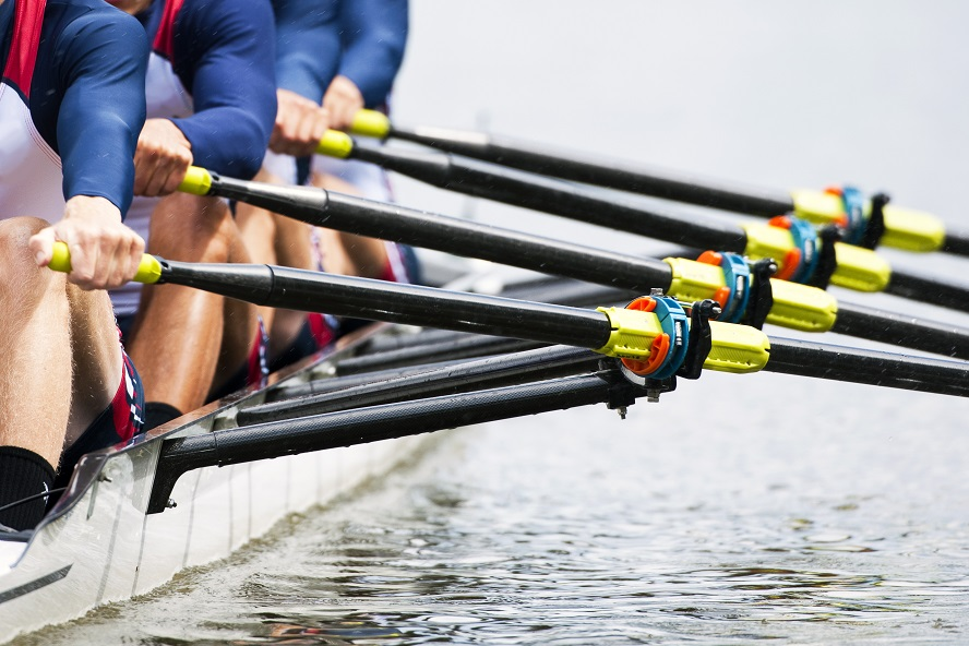 A close up shot of a men's rowing tea, focusing on the oars and hull