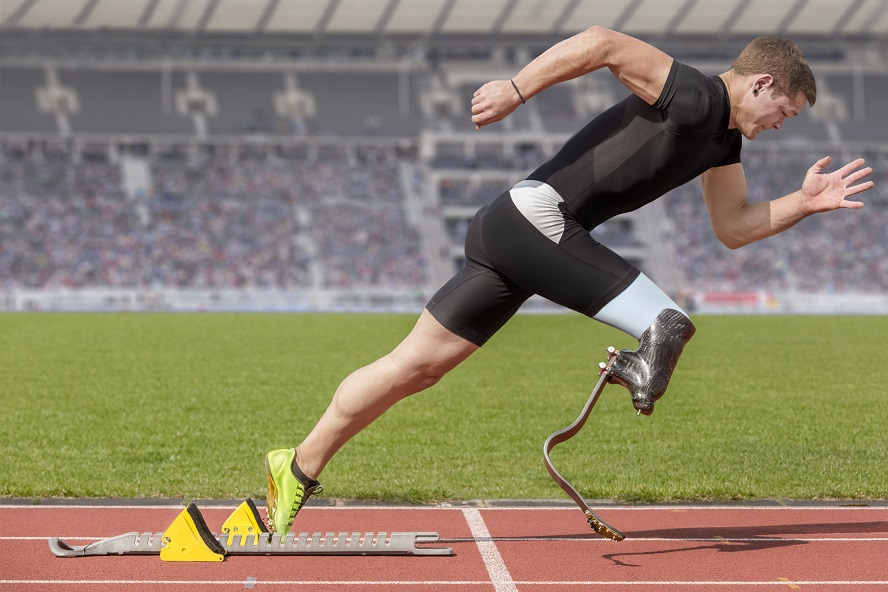 A sprinter with an amputated leg that has been replaced by a prosthetic blade leaving the starting block