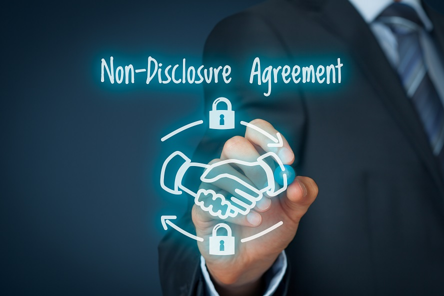 A hand drawing a non disclosure agreement