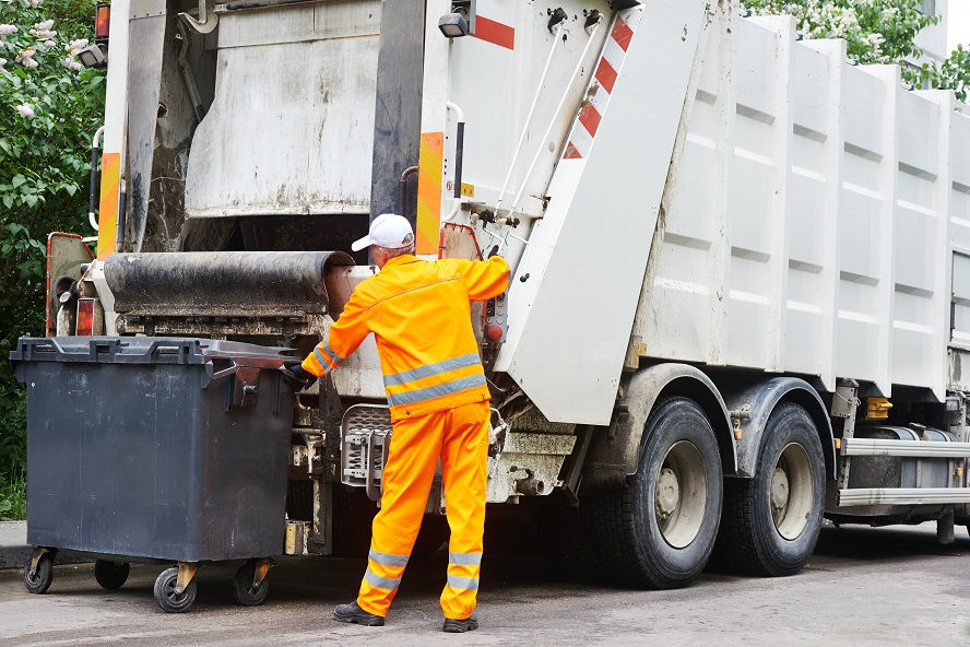 A garbage man loading up a garbage truck