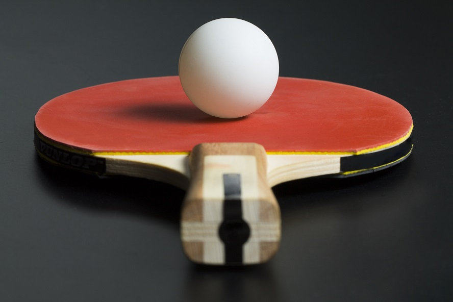 A table tennis bat with a ping pong ball resting on top of it